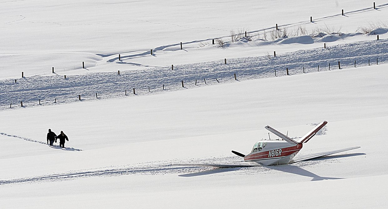 A woman is escorted from a fixed wing, single-engine airplane, which crashed just off the north end of runway at Steamboat Springs Airport in Steamboat Springs Friday afternoon.