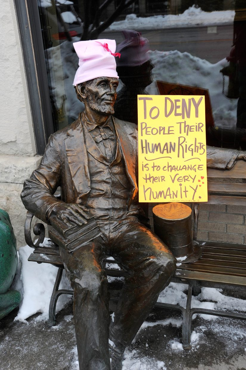 A sign is placed next to the Abraham Lincoln statue on Lincoln Avenue during the Women's March on Steamboat Springs.