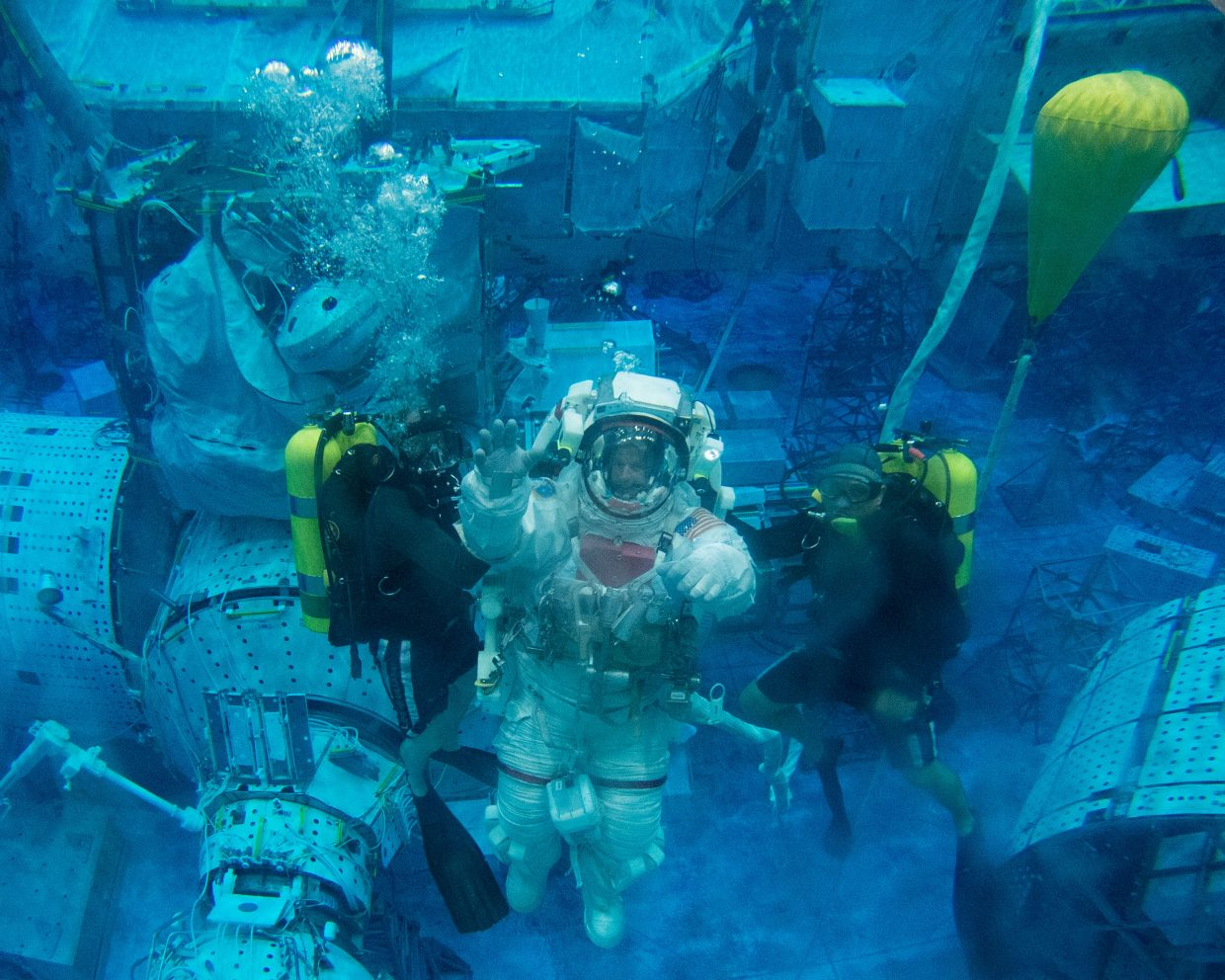 NASA astronaut Steve Swanson participates in a spacewalk training session in the waters of the Neutral Buoyancy Laboratory near NASA's Johnson Space Center. Divers are in the water to assist Swanson in his rehearsal, which is intended to help prepare him for possible work on the exterior of the International Space Station.