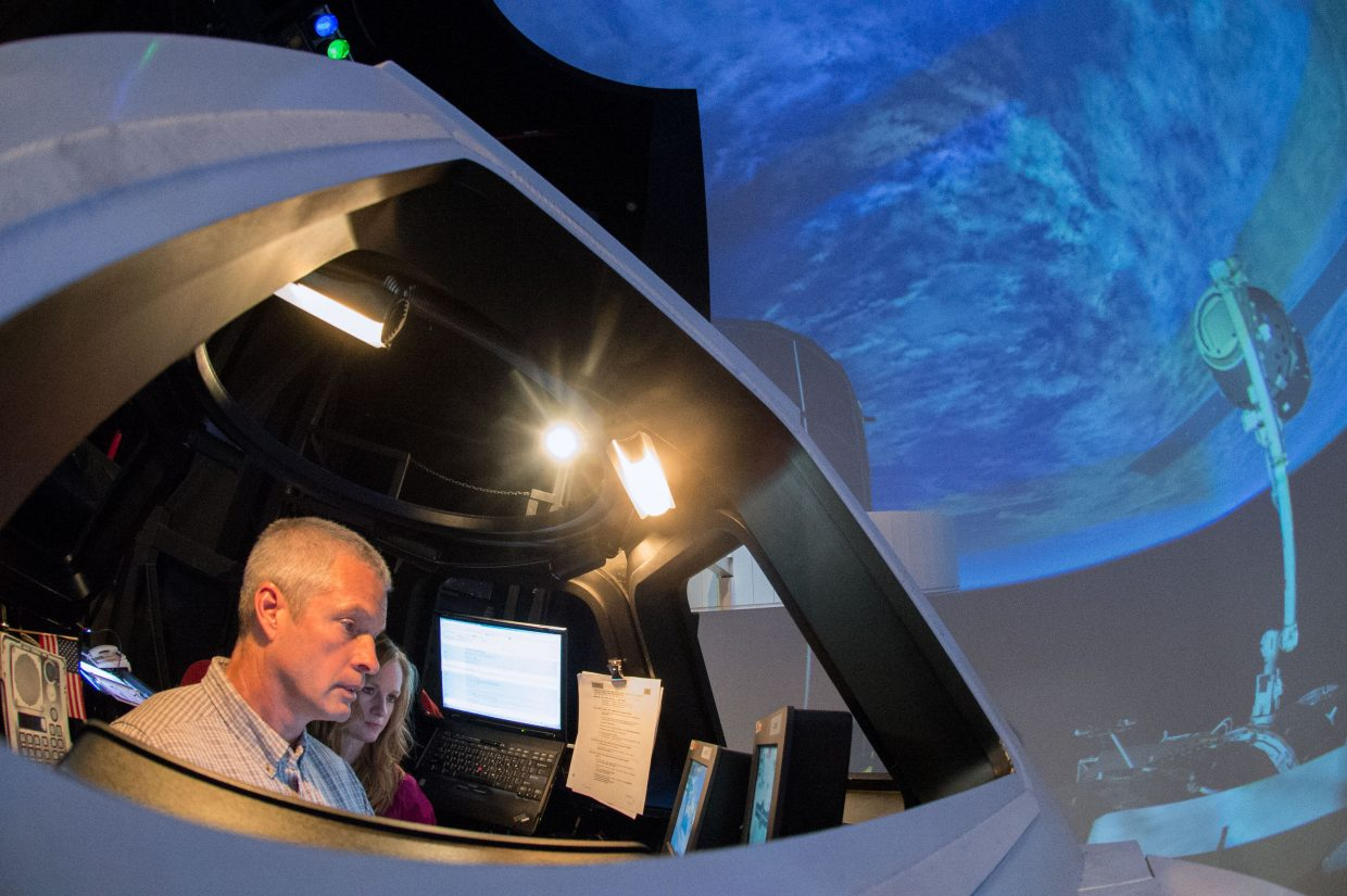 NASA astronaut Steve Swanson participates in an exercise in a Cupola trainer in the systems engineering simulator in the Avionics Systems Laboratory at NASA's Johnson Space Center. The facility includes moving scenes of full-sized International Space Station components over a simulated Earth.