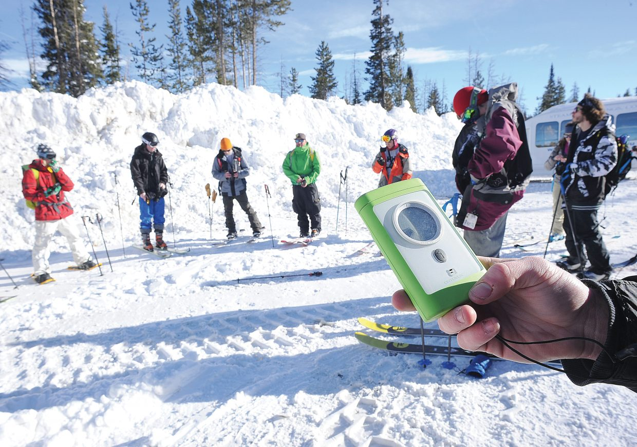 Students review the proper use of an avalanche beacon before trekking into the backcountry at the top of Rabbit Ears Pass for an avalanche awareness class.