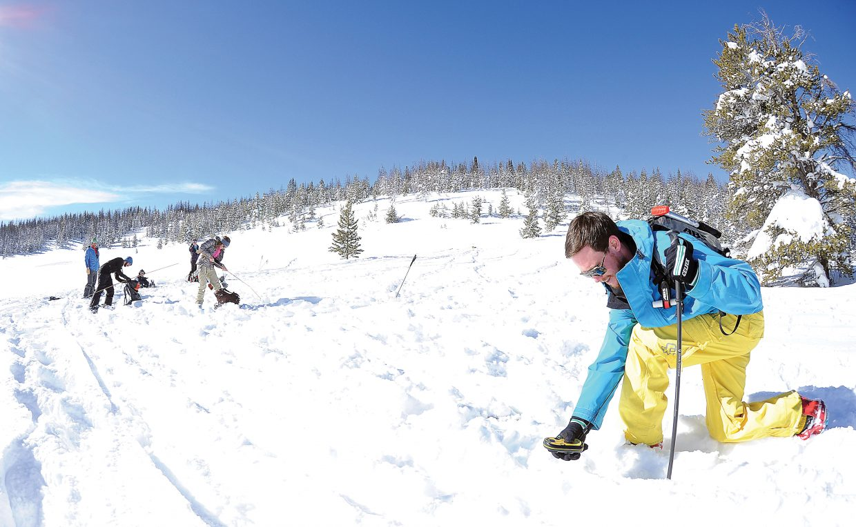 Student Drew Vaughn uses an avalanche beacon to locate another beacon that had been buried under the snow at a training site at the top of Rabbit Ears Pass. The students were taking part in an avalanche awareness class offered by Colorado Mountain College. The course was a mix of in-class and field learning.