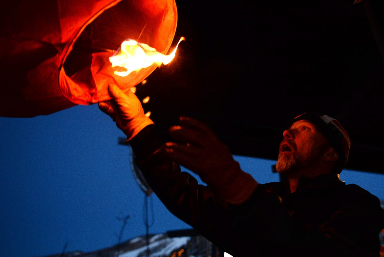 Craig Robinson lets go of a flying lantern Saturday at Steamboat Ski Area during the Olympic send off event.