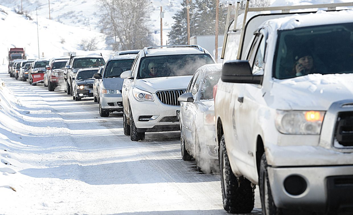 Cars wait in a long line in front of the Snow Bowl Plaza while rescue crews work to clear an accident half a mile down the road in front of the KOA campground. Drivers were faced with difficult, icy conditions Monday morning that caught many drivers off guard.