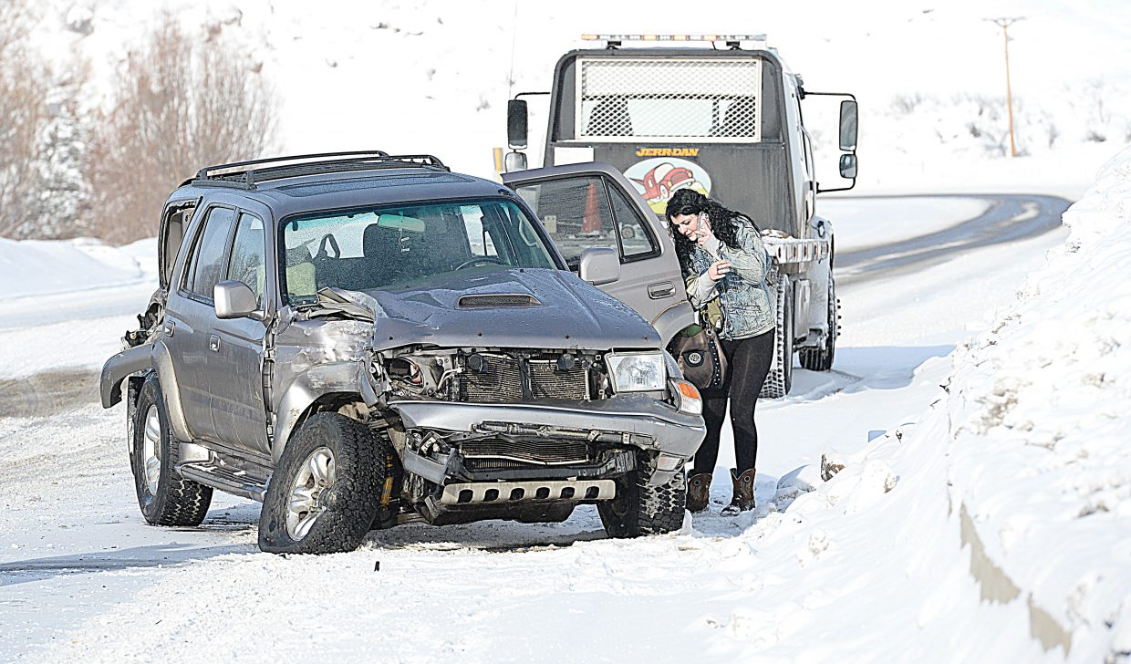 The driver of this sports utility vehicle pulls belongings out of the back seat after being involved in a multiple vehicle accident near the Steamboat Springs KOA campground Monday morning. Driving conditions at the time of the accident were difficult with a thin layer of ice making it nearly impossible to stop and difficult to keep vehicles under control around the curve where the accident happened. This accident was one of seven along U.S. Highway 40 at that time, including one crash in front of Steamboat II, which resulted in two people being transported by ambulance to Yampa Valley Medical Center.
