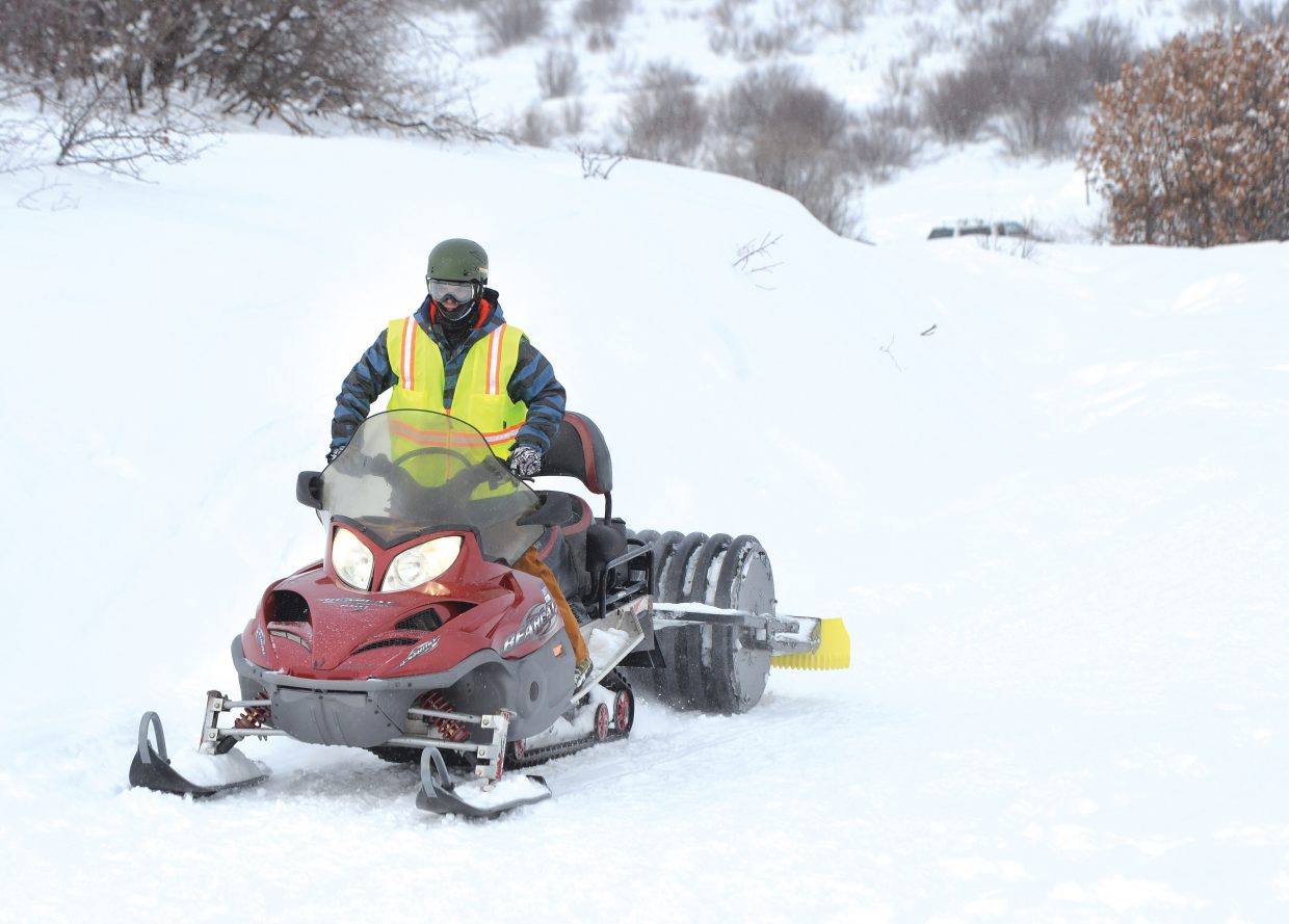 Mark Martinez uses a snowmobile to groom the snow on the trails at Howelsen Hill for fat bike riders looking to get out in the winter. On Wednesday, Martinez was grooming trails from Blackmere Drive to the quarry and back.