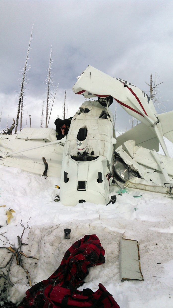 """The wreckage of Mark Darling's plane is inspected at the crash site south of Rabbit Ears Pass. Darling's son said the survivor was doing """"amazingly well"""" at a Denver hospital after being rescued after the crash."""
