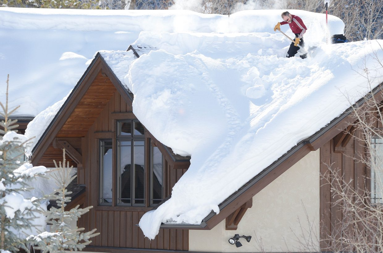 """Jeff Good, who runs a property management company in Steamboat Springs, shovels snow from the roof of a home near the Rollingstone Ranch Golf Club in Steamboat Springs. Good said he was shoveling the snow away from the """"doghouses,"""" which are located at the top of the roof and help cool air circulate under the roof's outer surface. Good said good air circulation is the key to preventing ice dams in this part of the Colorado Rockies."""