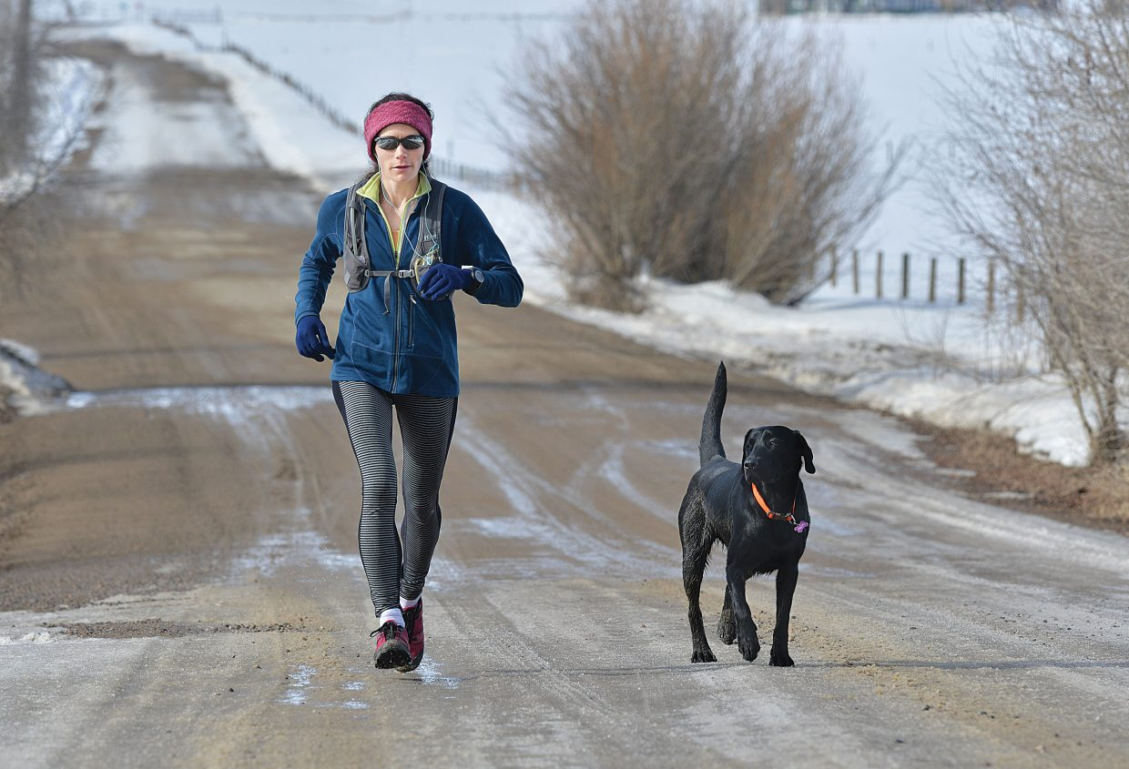Amanda Taglioli and her dog Maggie make their way along Routt County Road 42 on Thursday morning. Taglioli said she was making the most of the Yampa Valley's warm weather, despite the patches of mud along the road.