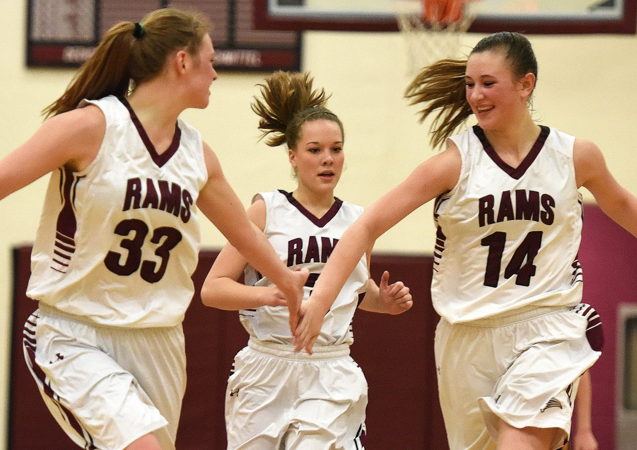 Jessica Rossi, left, Kali Constine and Briana Peterson celebrate a basket late in Saturday's win against West Grand. The Rams improved to 13-2 with the win and avenged one of those two losses.