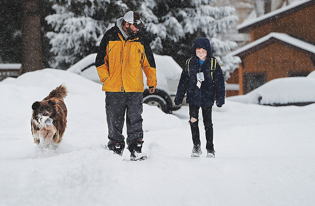 Kevin Comstock and Willow escort Liam Hine, right, to school during Monday's snowstorm.