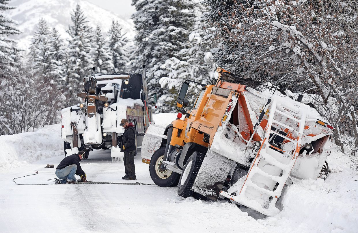Tow truck driver John Layman attaches a chain to the front of a city of Steamboat Springs plow truck Tuesday morning before attempting to pull the fully loaded vehicle from a drainage ditch along Steamboat Boulevard. The driver was attempting to push back the piles of snow that collect along the roadways when the tires got caught in the ditch and pulled the truck into the drainage. The road was temporarily closed while crews worked to remove the vehicle from the ditch.
