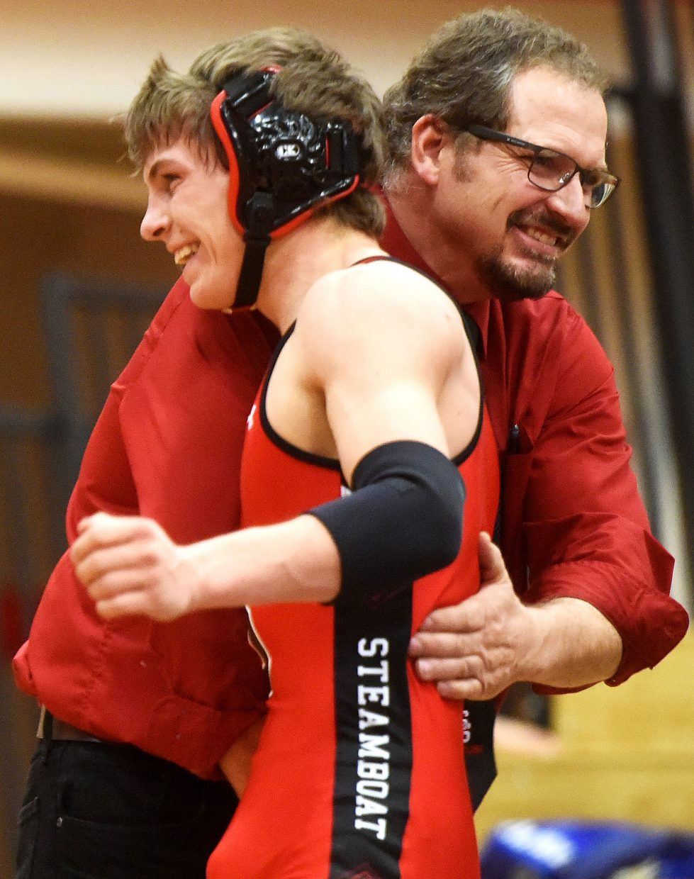 Coach Travis Bryant and his son, Lance Bryant, share a moment after Lance won a tight match Thursday against Palisade.