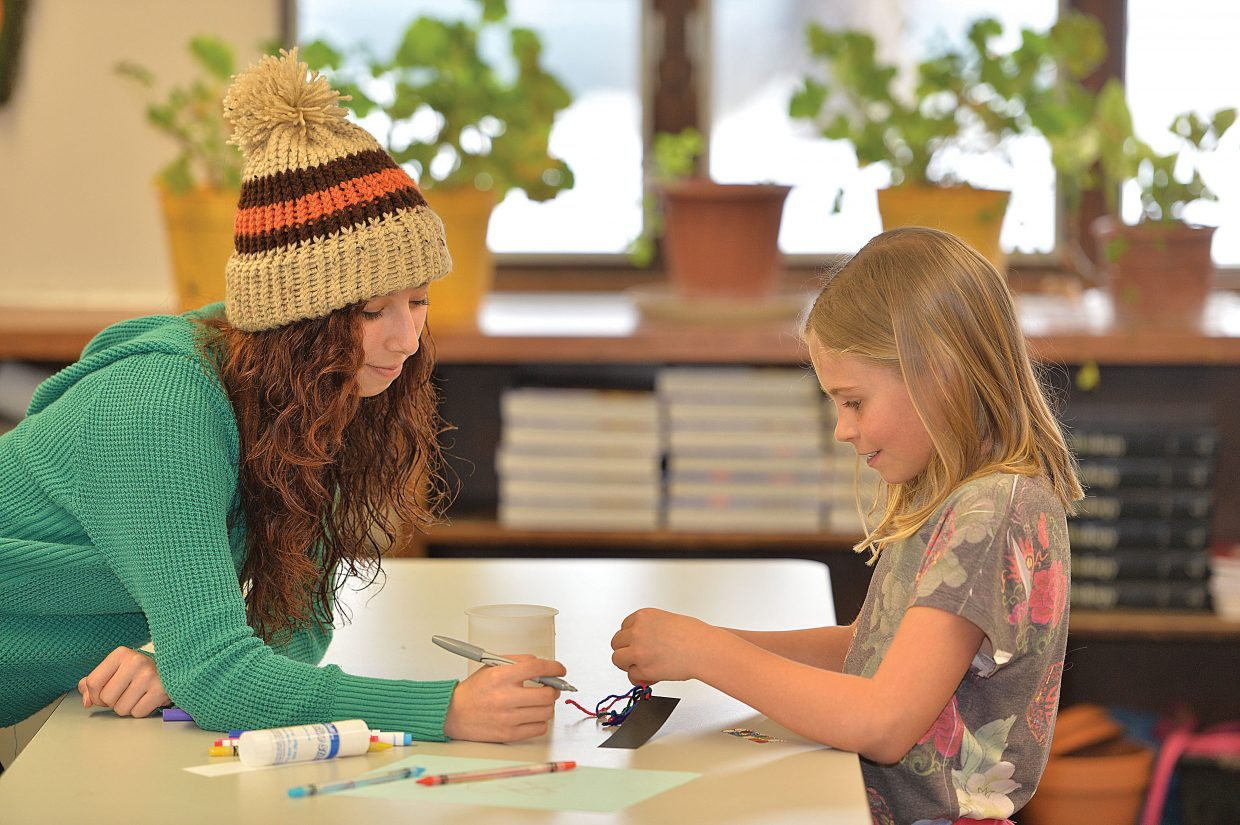 Yampa Valley High School student Angel Ballesteros and Soda Creek Elementary School third-grader Evan Quinn make bookmarks together at the high school in 2015.