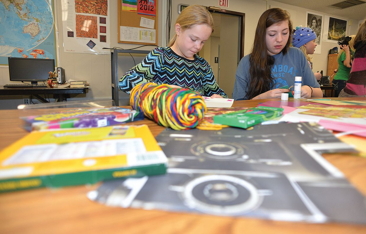 Soda Creek Elementary School third-grader Morgan Kopischke and Yampa Valley High School student Montana Malburg make bookmarks Wednesday morning as part of Students Rebuild's Literacy Challenge, which inspires students around the world to make bookmarks to benefit Save the Children's Literacy Boost program.