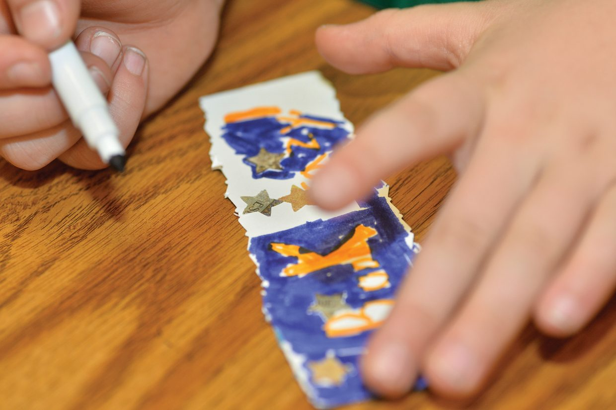 Soda Creek Elementary School third-grader Tommy Landers creates a bookmark Wednesday morning as part of Students Rebuild's Literacy Challenge, which inspires students around the world to make bookmarks to benefit Save the Children's Literacy Boost program.