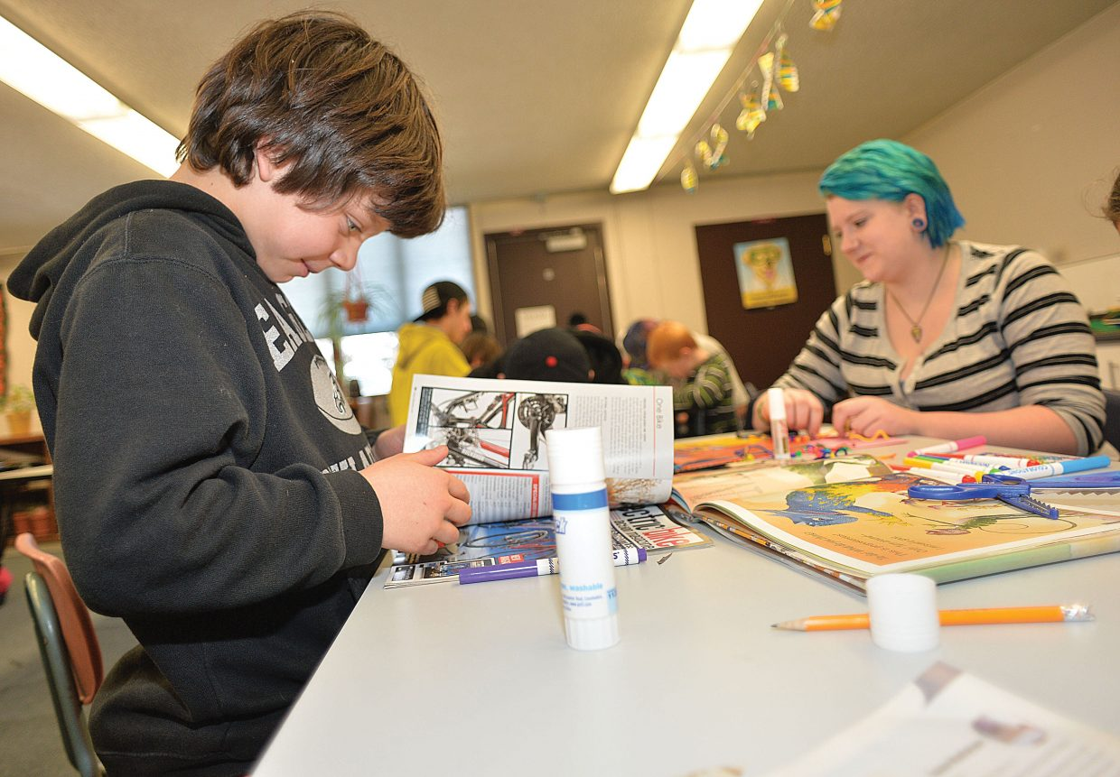 Soda Creek Elementary School third-grader William Harbinson flips through some magazines for images for his bookmark. The third-graders joined Yampa Valley High School students to create the bookmarks Wednesday morning as part of Students Rebuild's Literacy Challenge.