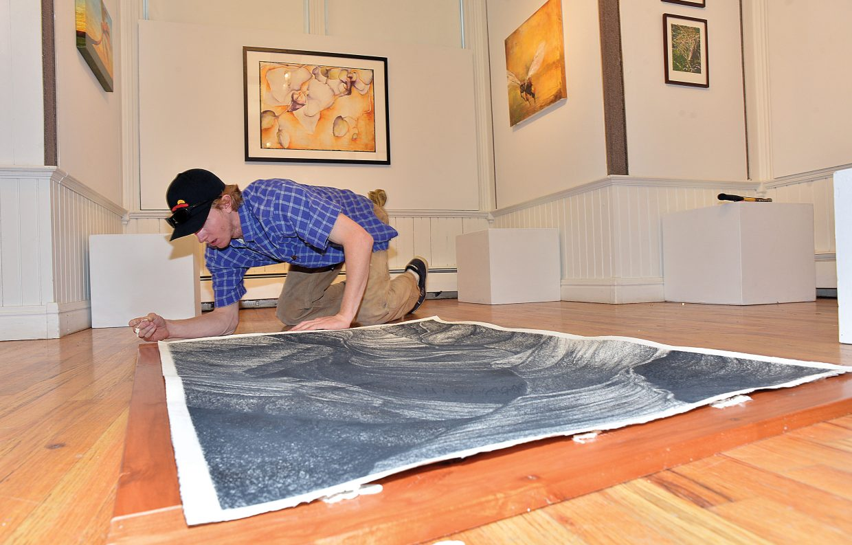 Local artist Malcolm Perkins-Smith works hanging a new show at the Depot Art Center in downtown Steamboat Springs. Palettes: A Taste for the Senses will open Friday and will feature the work of several top local artists.