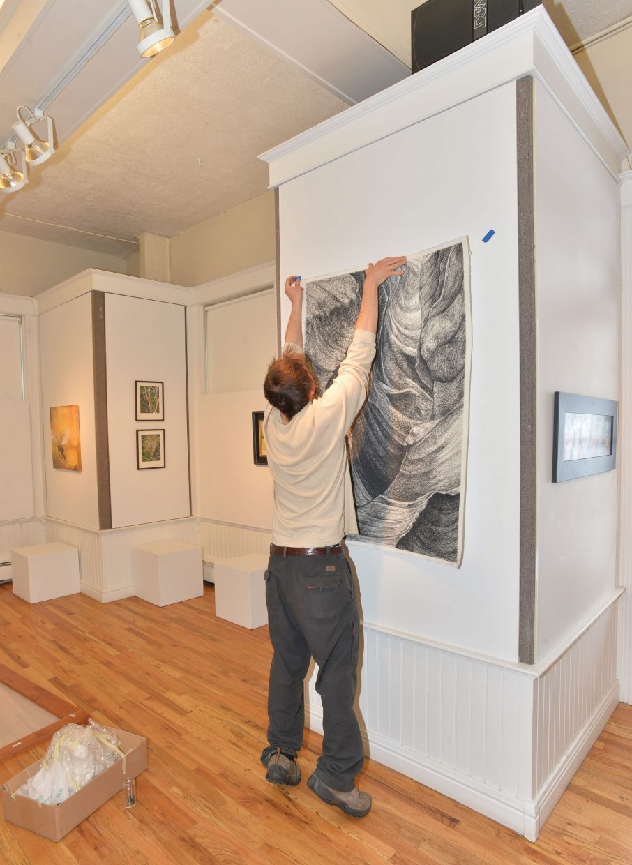 Local artist Greg Block hangs a piece of work by Sista Luna at the Depot Art Center in downtown Steamboat Springs.