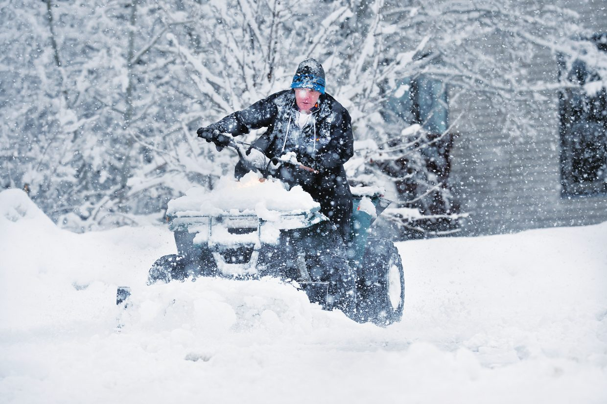 Kevin Marsden uses his four-wheeler to plow the snow off the road in Conifer Circle Wednesday morning. Steamboat residents woke up to several inches of snow on the ground, and it was still falling.