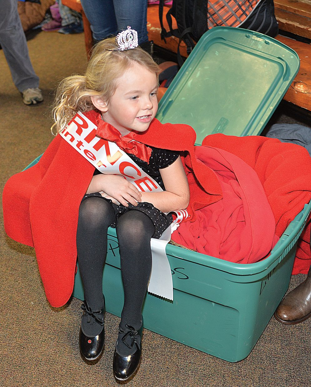 """Jordyn Lottes sits in a box of capes prior to the start of Wednesday night's Winter Carnival Opening Ceremonies. The evening, which included Winter Carnival Royalty, the princesses and an appearance by Jon Banks the """"Lighted Man"""", kicks off the 102nd annual Steamboat Springs Winter Carnival."""