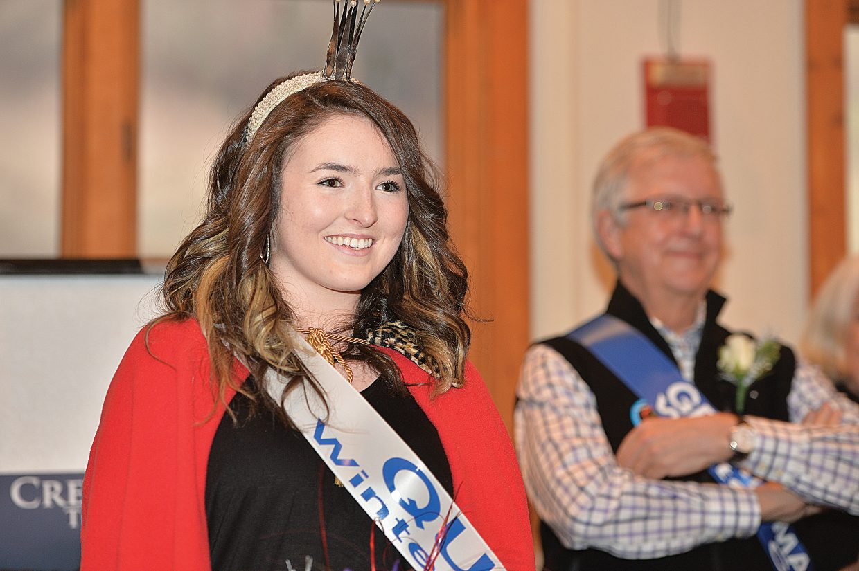 Winter Carnival Queen Maggie Carrigan smiles after taking her place at the front of Olympian Hall during Wednesday evening's Winter Carnival opening ceremonies. Ellese Lupori, this year's junior attendant, and Ester Rose DelliQuadri, this year's sophomore attendant, joined Carrigan.
