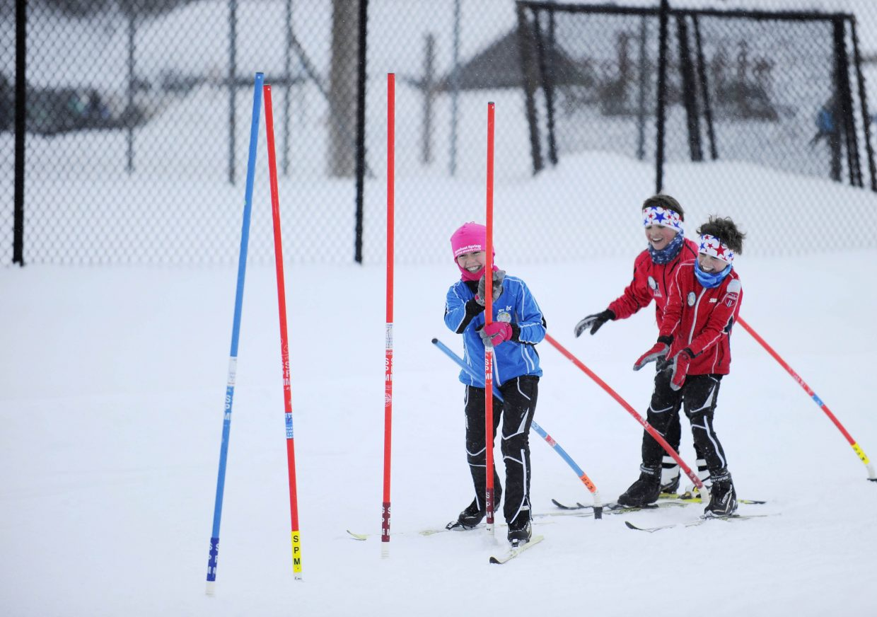 Steamboat Springs Winter Sports Club athletes, from left, Suzy Magill, Grey Barbier and Henry Magill race in the obstacle course Thursday night during Winter Carnival festivities at Howelsen Hill.