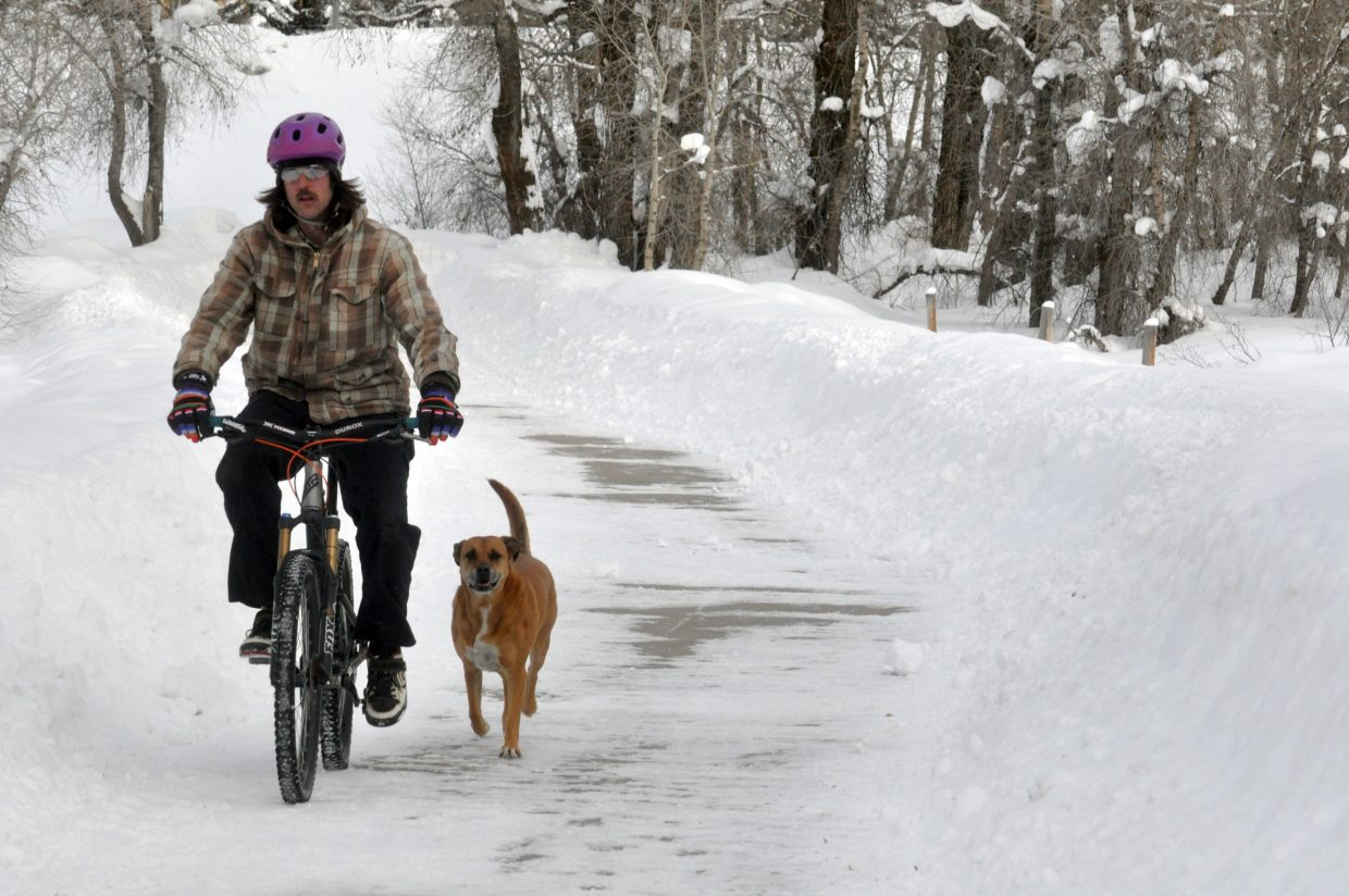 Matt Spady bikes on the Yampa River Core Trail with his dog Kouli at his side. After wrestling with the decision Wednesday, the trails lodging tax committee decided the extension of the trail to the south is not a top priority.