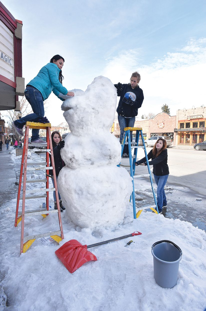 """Steamboat Springs High School students Jennifer Maldonado, on the right on top of the ladder, Shannon Day, middle right, Gabi Seng, on the left on top of ladder, and Kennedy Mattson put the finishing touches on their sculpture of Olaf, from the Disney movie """"Frozen."""" The high school students design the creations and then spend part of the day building them along Lincoln Avenue as part of a time-honored tradition."""