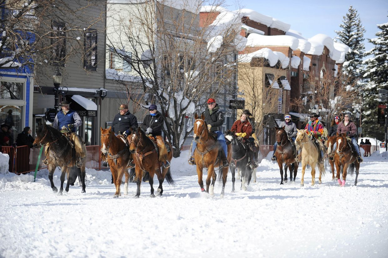 Local ranchers ride horses down Lincoln Avenue during Winter Carnival.
