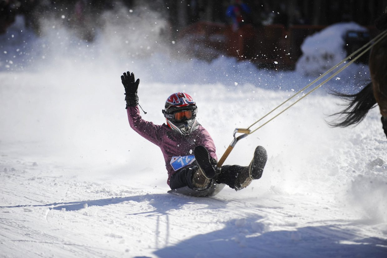 Michelle Barnes holds on during the Winter Carnival shovel race Saturday.