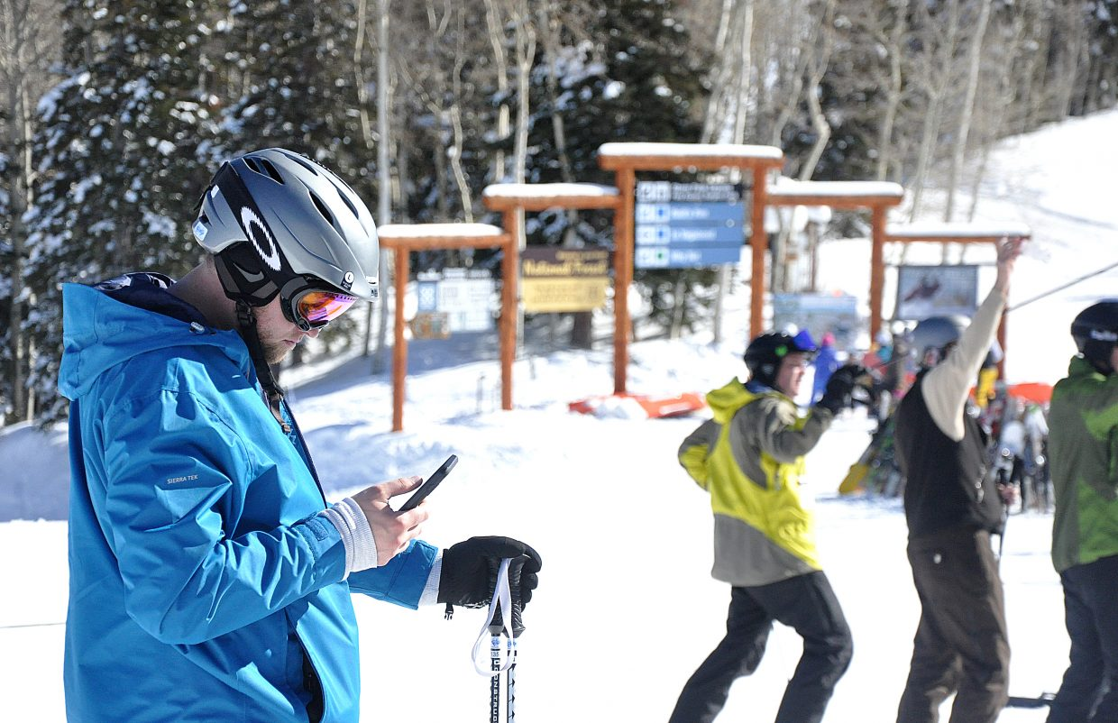 Skier Brandon Scharn, of Dallas, checks his work email on his smartphone on Friday afternoon outside of the Thunderhead Lodge at the Steamboat Ski Area. Ski areas are upgrading their wireless infrastructure to accommodate a generation of skiers that has grown closer to smartphones.