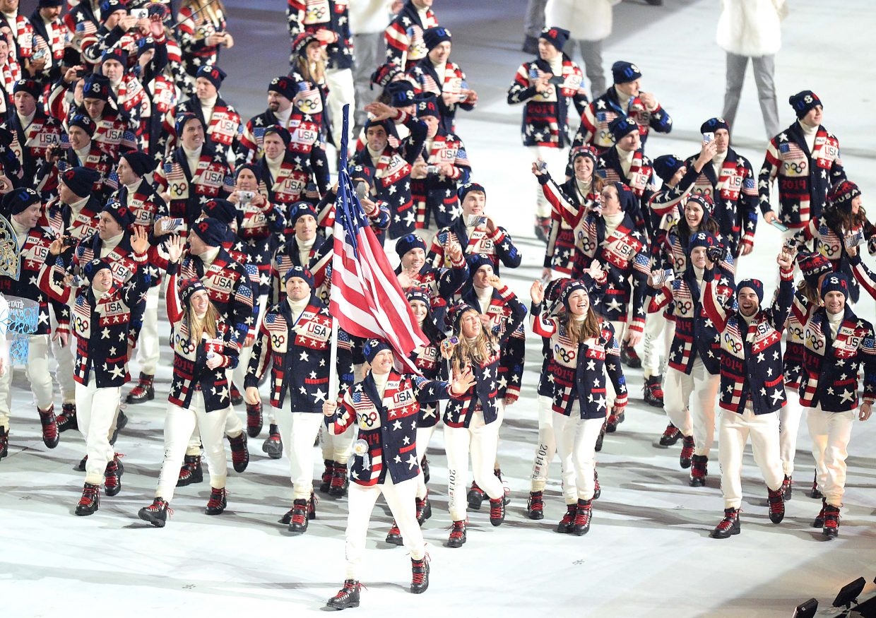 Steamboat Springs Nordic combined athlete Todd Lodwick carries the American flag and leads the United States Olympic Team into Fisht Olympic Stadium on Friday night during the Opening Ceremonies of the 2014 Winter Olympics in Sochi, Russia. Lodwick, competing in his sixth Winter Olympics, led the team up a ramp that had dropped down from the middle of the floor, then ran ahead, waving the flag with one arm and to a packed, roaring stadium with the other. He then rejoined the front ranks of Team USA and walked with them step for step around the arena.