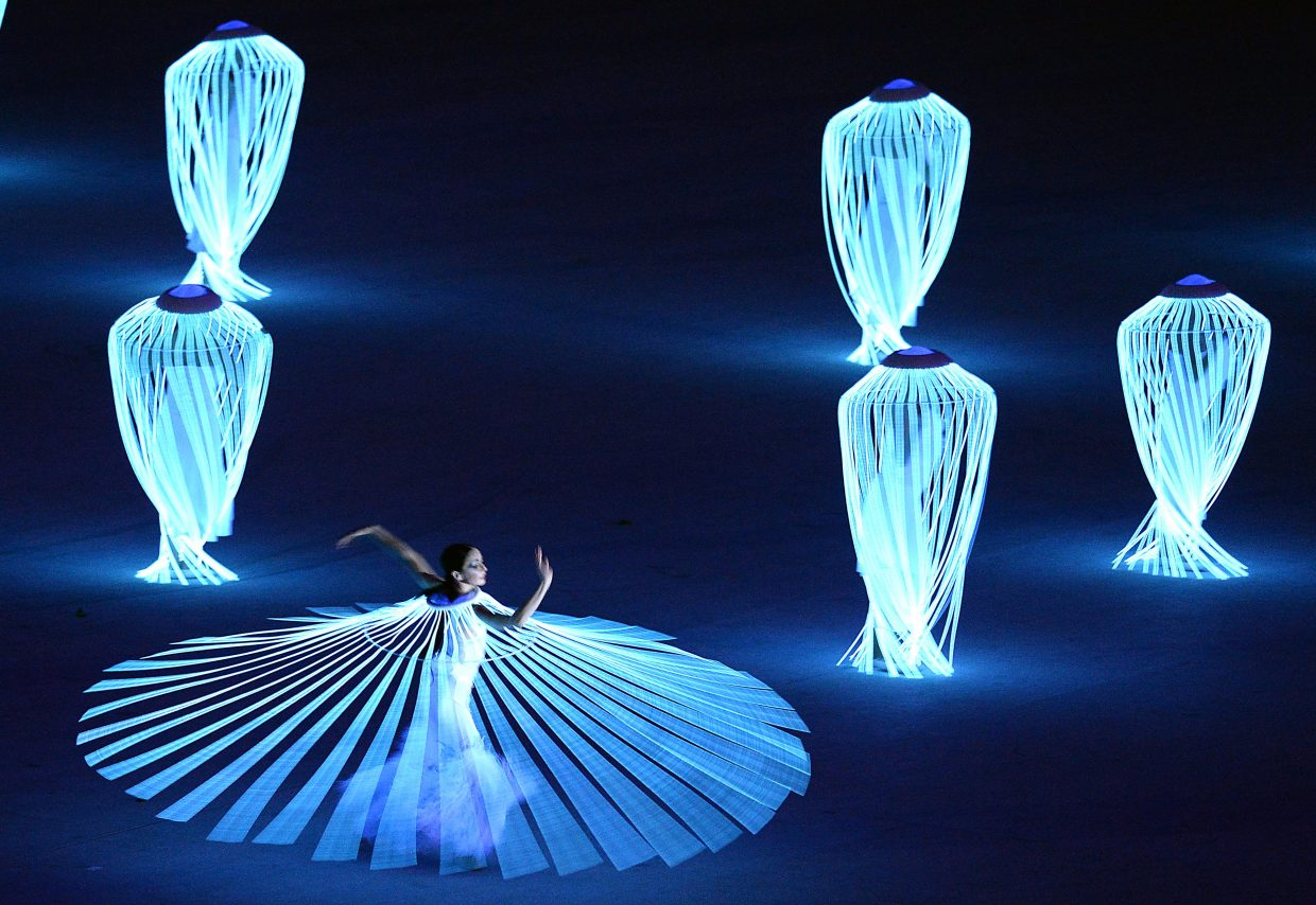 A twirling dancer spins with lights on Friday during the opening ceremony for the 2014 Winter Olympics.