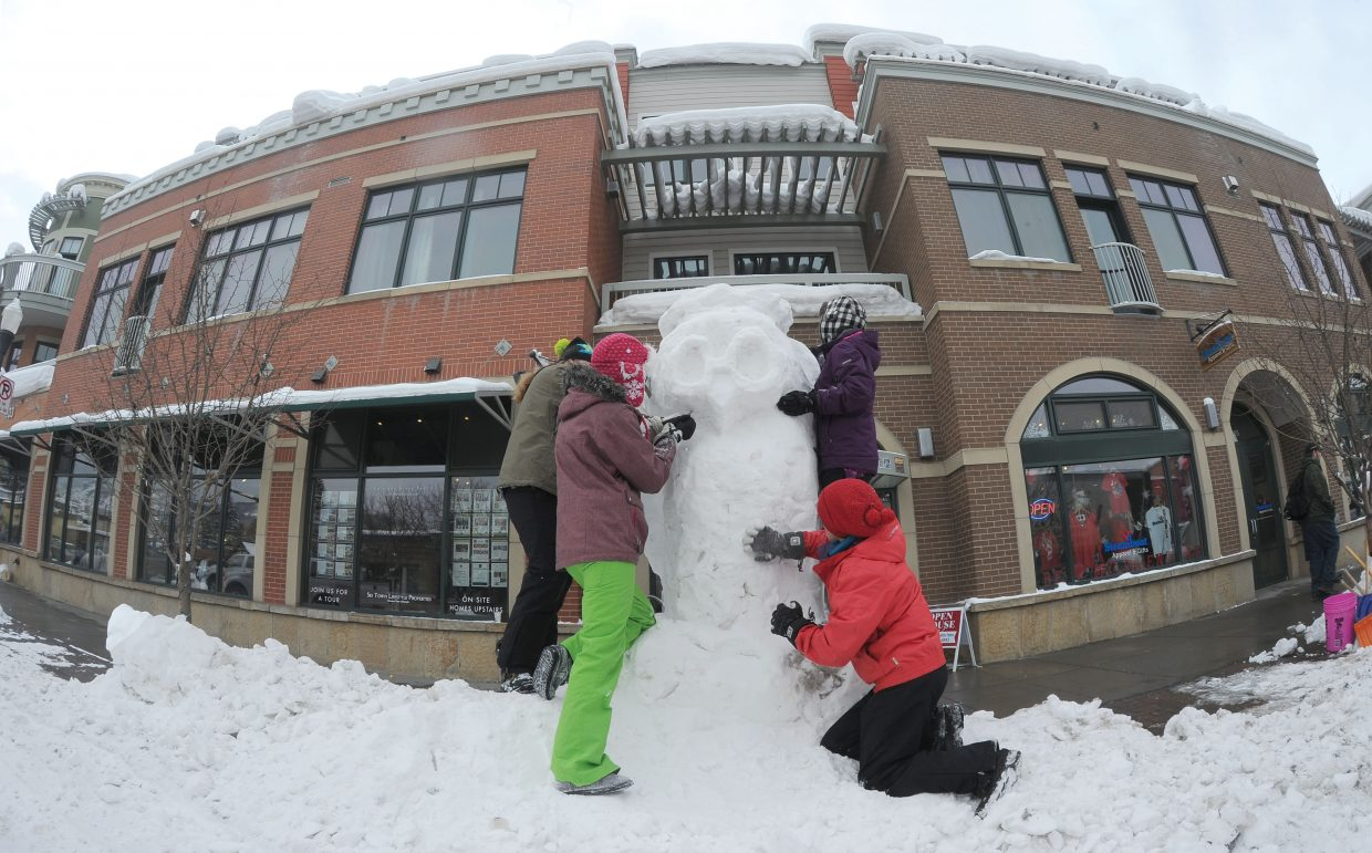 Steamboat Springs High School students, from left, Summer Dorr, Madi Owen, Payton Wendler and Casey Kirkendall work on a sculpture on Lincoln Avenue Thursday afternoon. The snow sculptures are a Steamboat Springs Winter Carnival tradition.