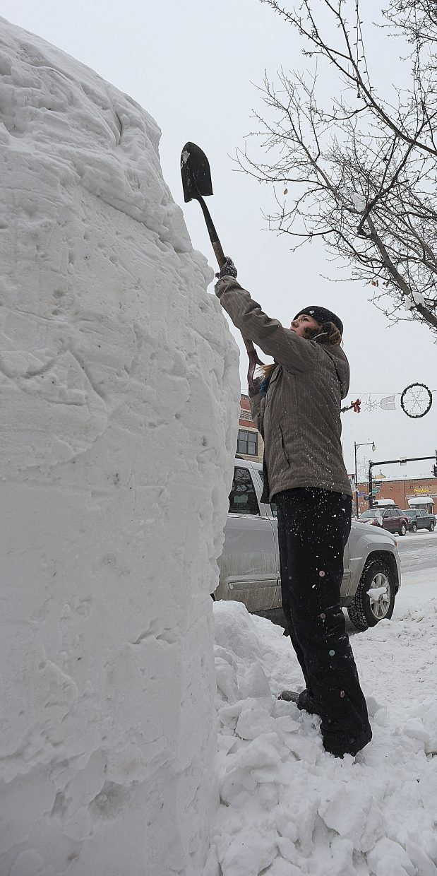 Steamboat Springs High School student Amber Finch uses a shovel to work on a snow sculpture on Lincoln Avenue Thursday morning. The snow sculptures are a Steamboat Springs Winter Carnival tradition.