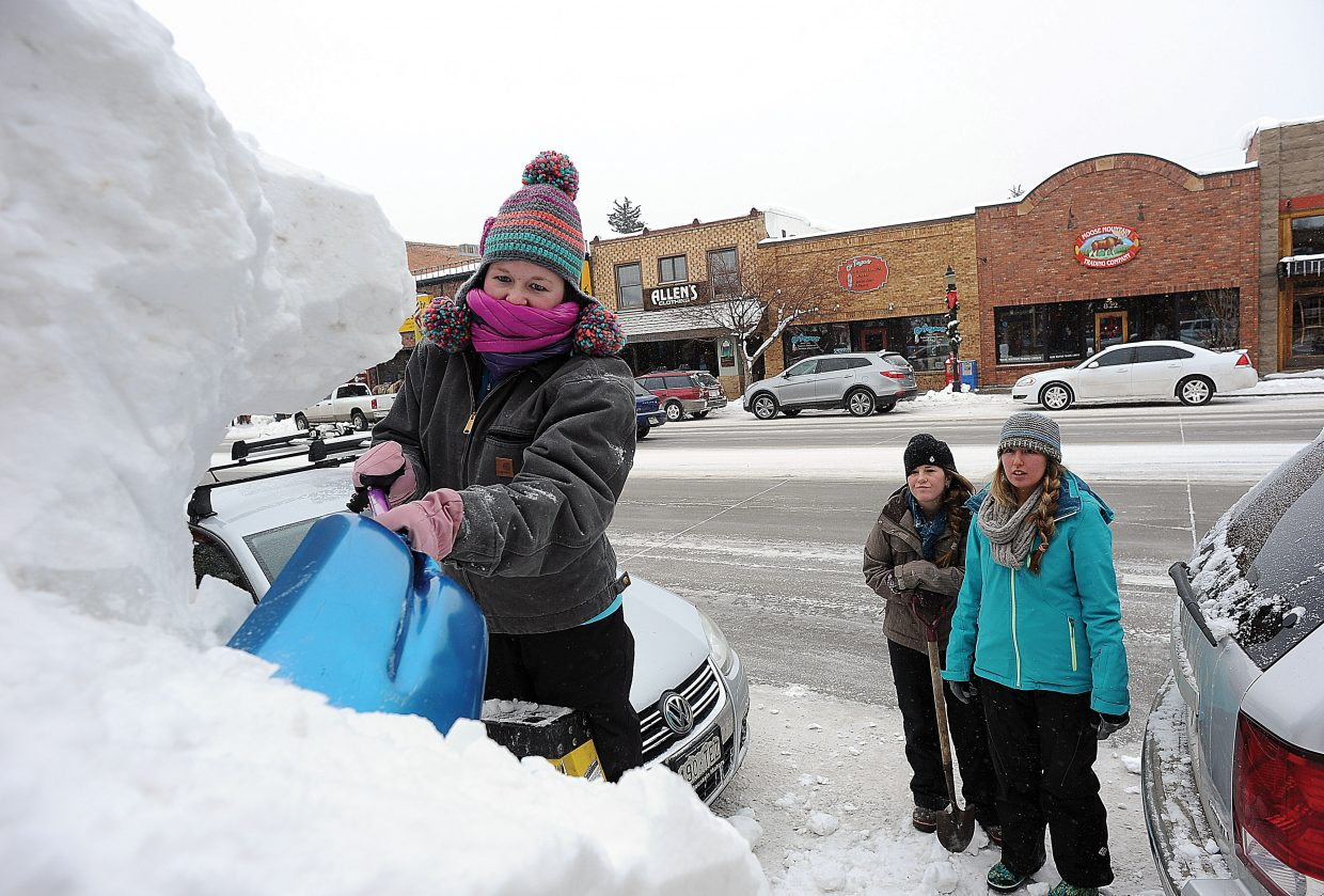 Steamboat Springs high school students Alexandra Waldschmidt (front, on ladder) Amber Finch (back, left) and Courtnee Weiss work on a snow sculpture on Lincoln Avenue Thursday morning. The snow sculptures are a Steamboat Springs Winter Carnival tradition.