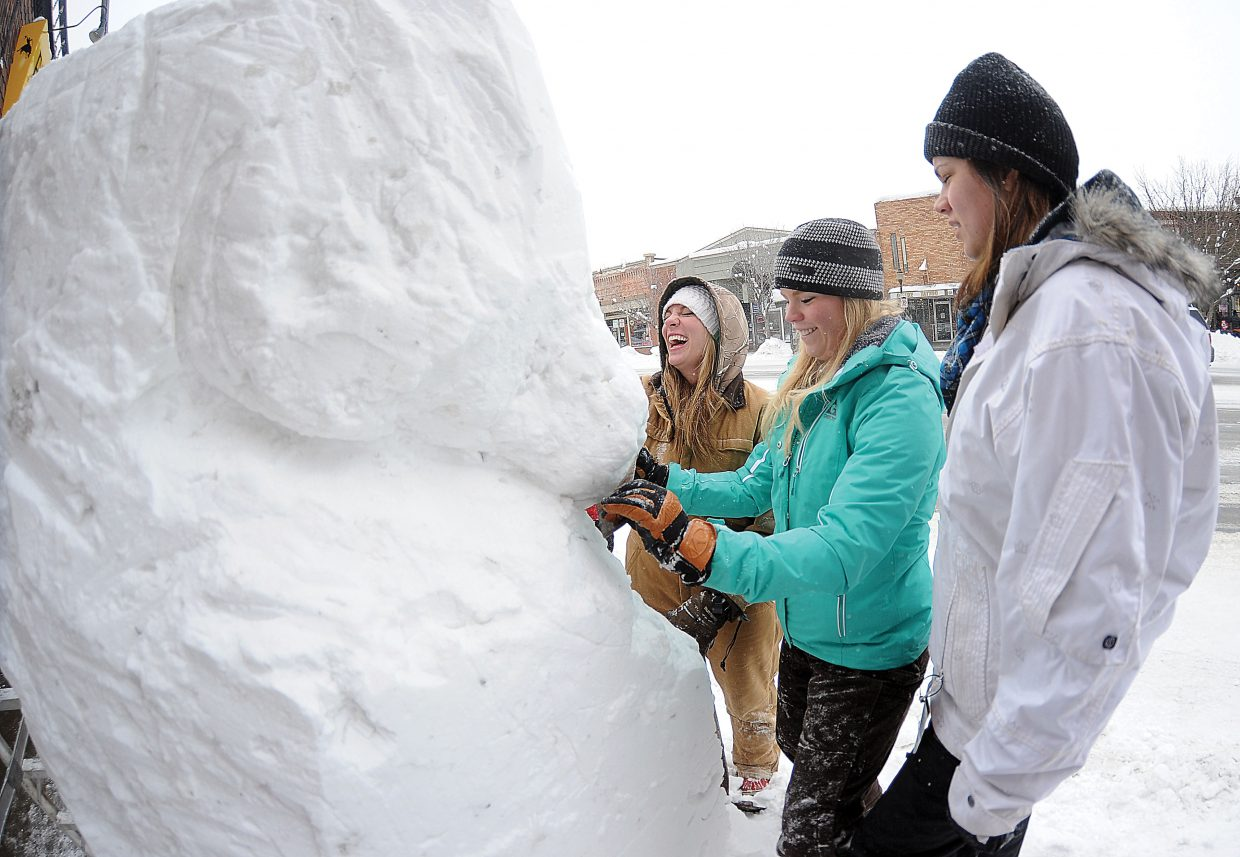 Danielle Haxton laughs while working on a snow sculpture with Mackenzie Holmberg, middle, and Andie Baker Thursday afternoon. The snow sculptures are a Steamboat Springs Winter Carnival tradition.
