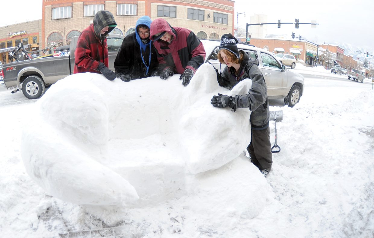 Steamboat Springs High School students, from left, Preston Anderson, Joe Hilterbrand, Jeffrey Seng and Levi Wynne work on a sculpture on Lincoln Avenue Thursday afternoon. The snow sculptures are a Steamboat Springs Winter Carnival tradition.