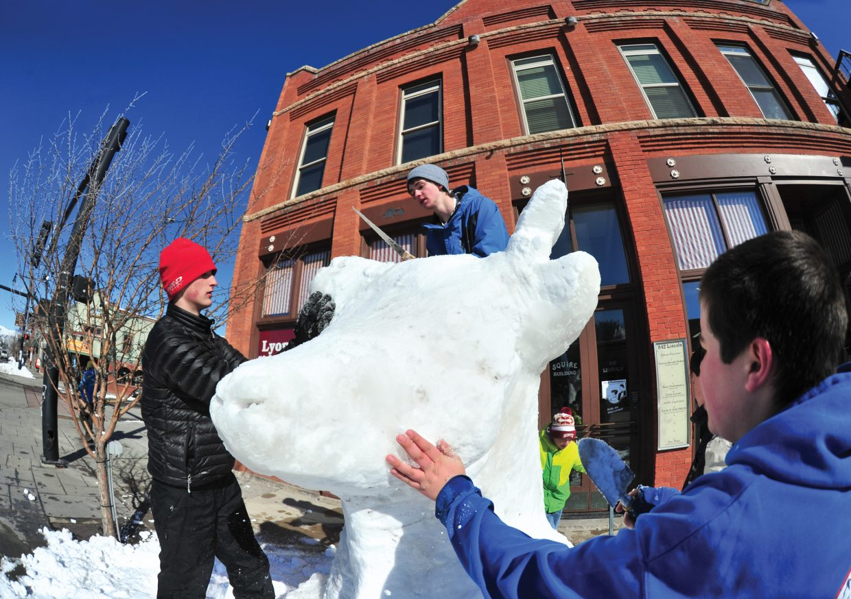 Steamboat Springs High School students Grant Andrews, far left, Drew Williamson, center, and Riley Brodie work on their group's snow sculpture for the 104th Winter Carnival.