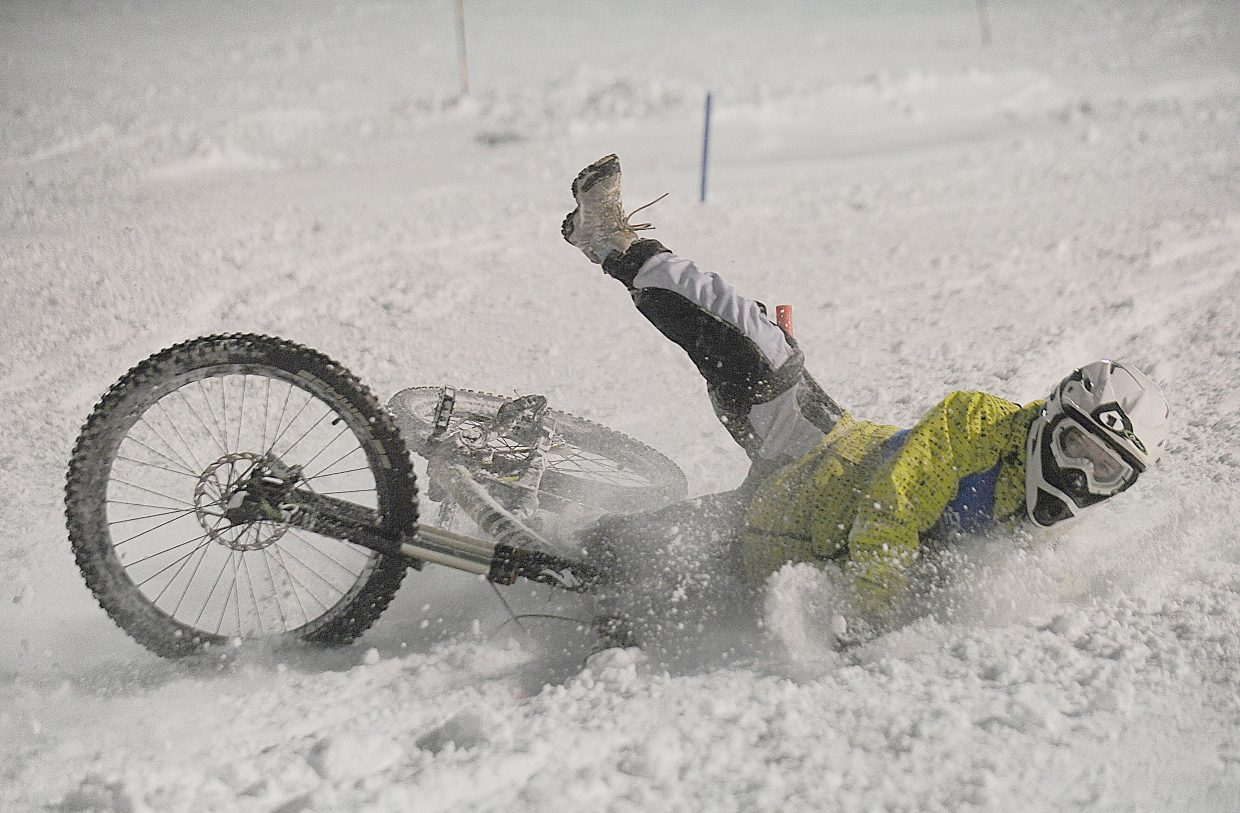 Jayden Haghebangh crashes during a practice run before the Winter Carnival dual slalom bike race Friday night at Howelsen Hill.