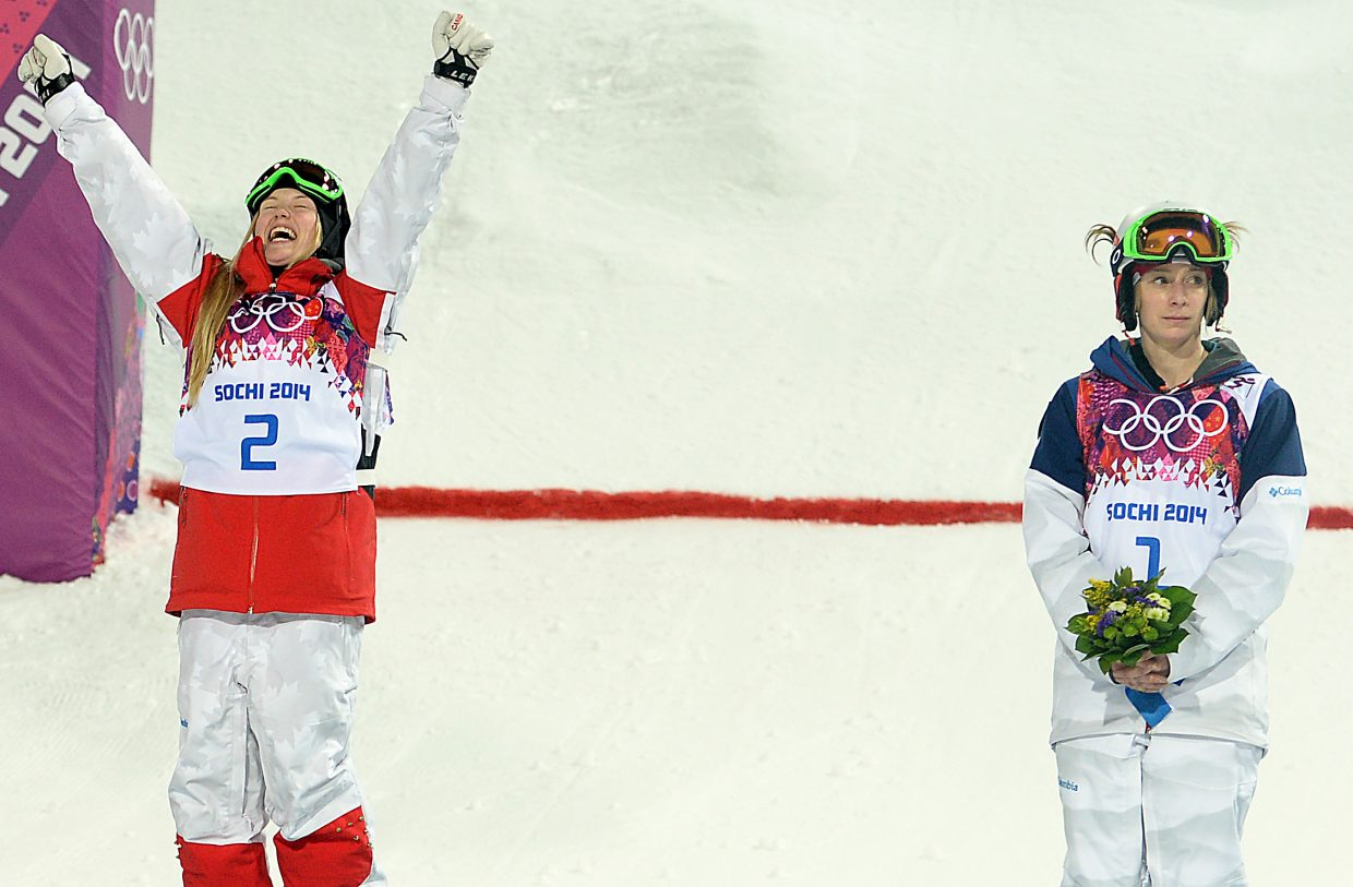 "Canada's Justine Dufour-Lapointe celebrates a gold medal as American Hannah Kearney looks on Saturday at the women's moguls finals at the 2014 Winter Olympics at Rosa Khutor Extreme Park in Russia. Kearney, who won gold in 2010 and has been a dominant force on the World Cup tour, had a bobble high on the course that cost her. Supporters shouted for her as she climbed on the podium, and she responded, ""I'm sorry."""