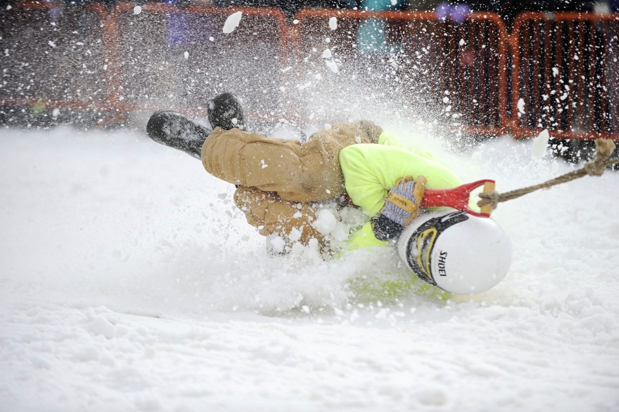 Andy Picking holds on tight while competing in the shovel race competition Saturday during the Winter Carnival street events.