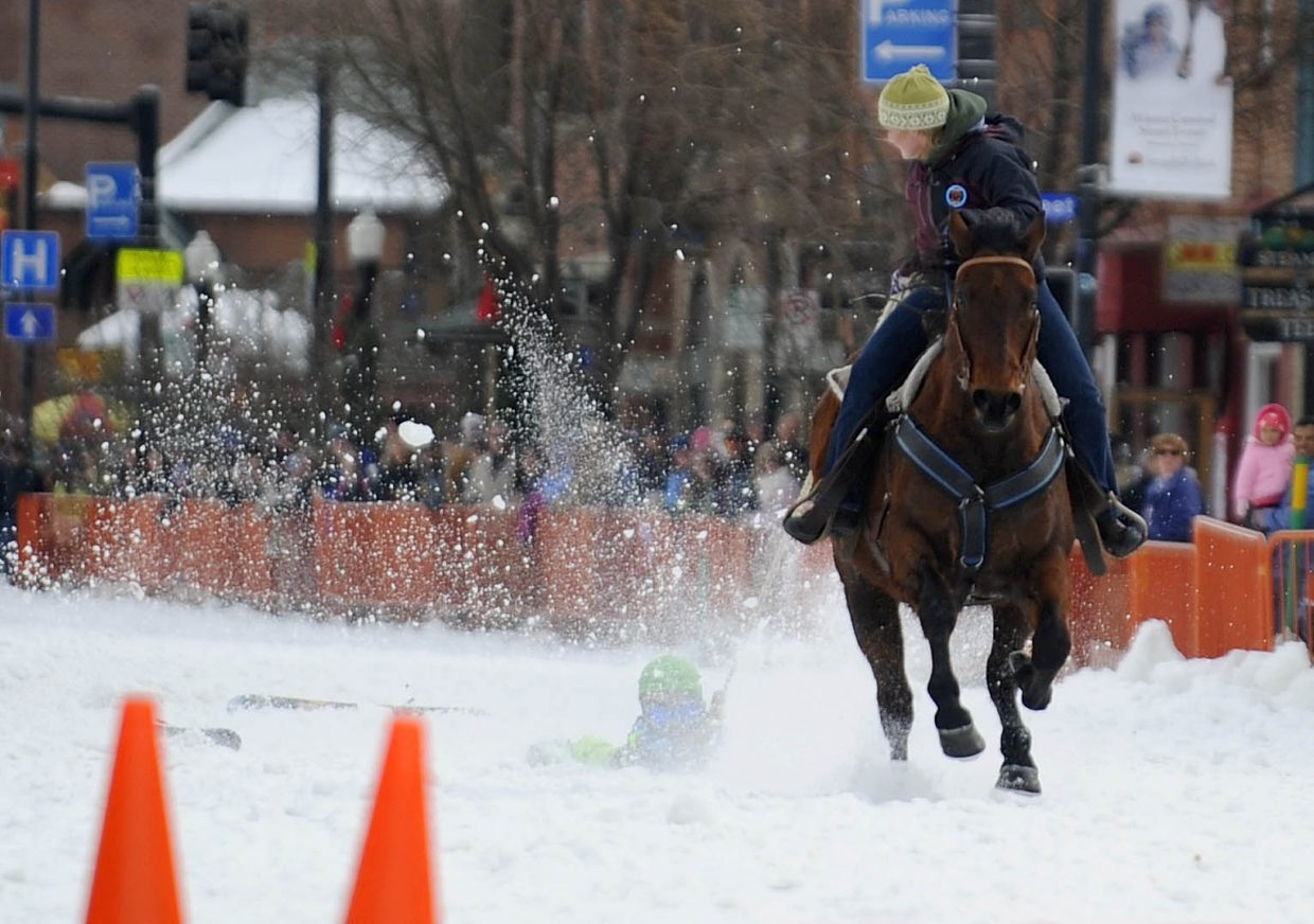 Scott Kane holds on after losing his skis during the donkey jump competition Saturday during the Winter Carnival street events.