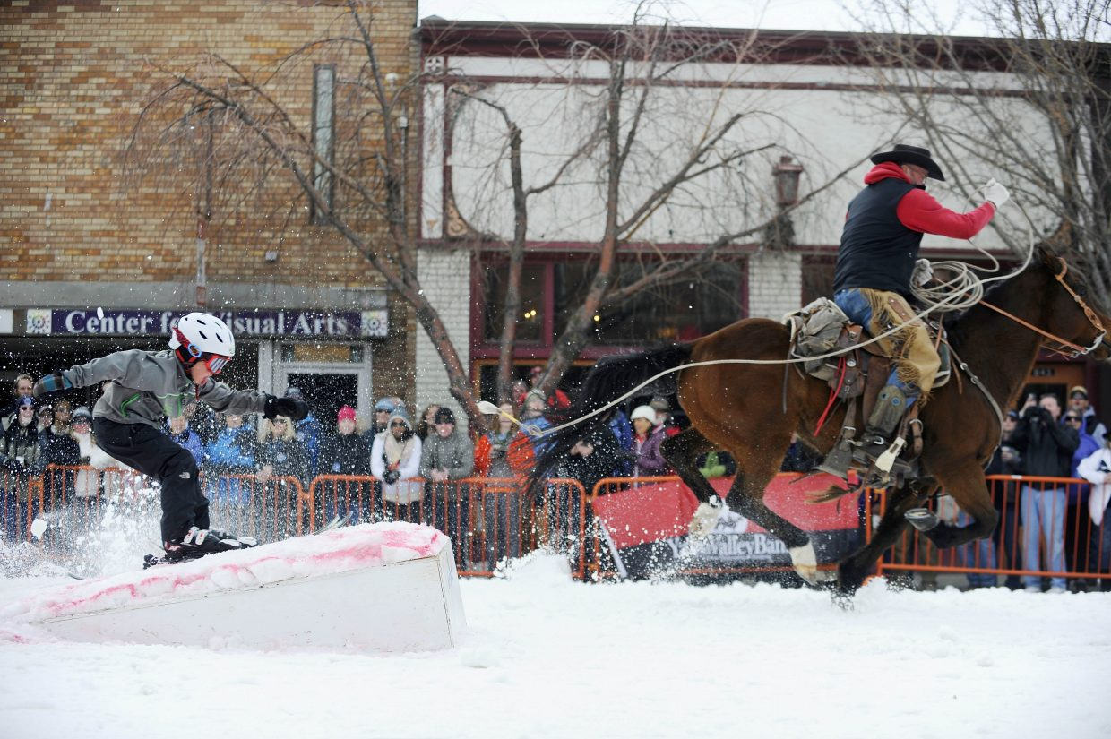 Doug Wheeler slings Koen Stroock up the jump during the donkey jump competition during Winter Carnival street events.