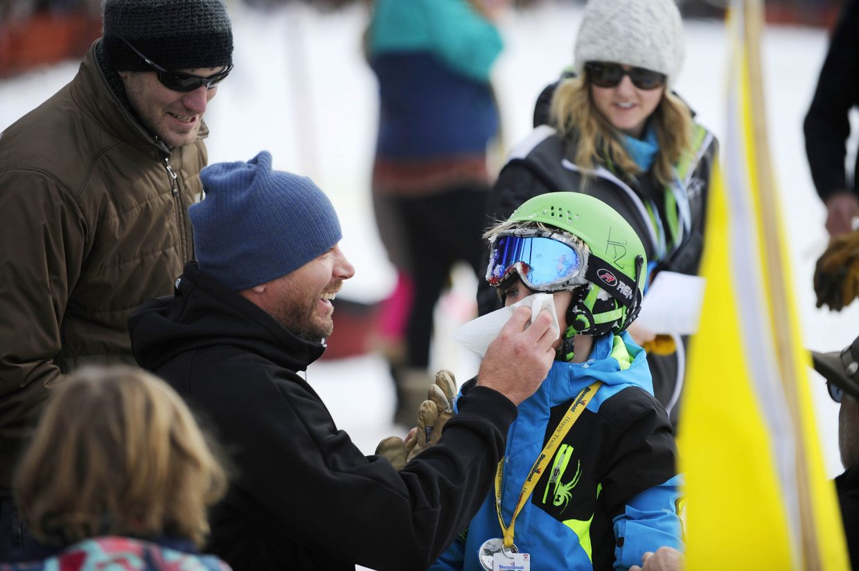 Matt Kane helps his son Scott with a bloody nose after Scott took a bumpy ride in the snow during the donkey jump competition Saturday during the Winter Carnival street events.