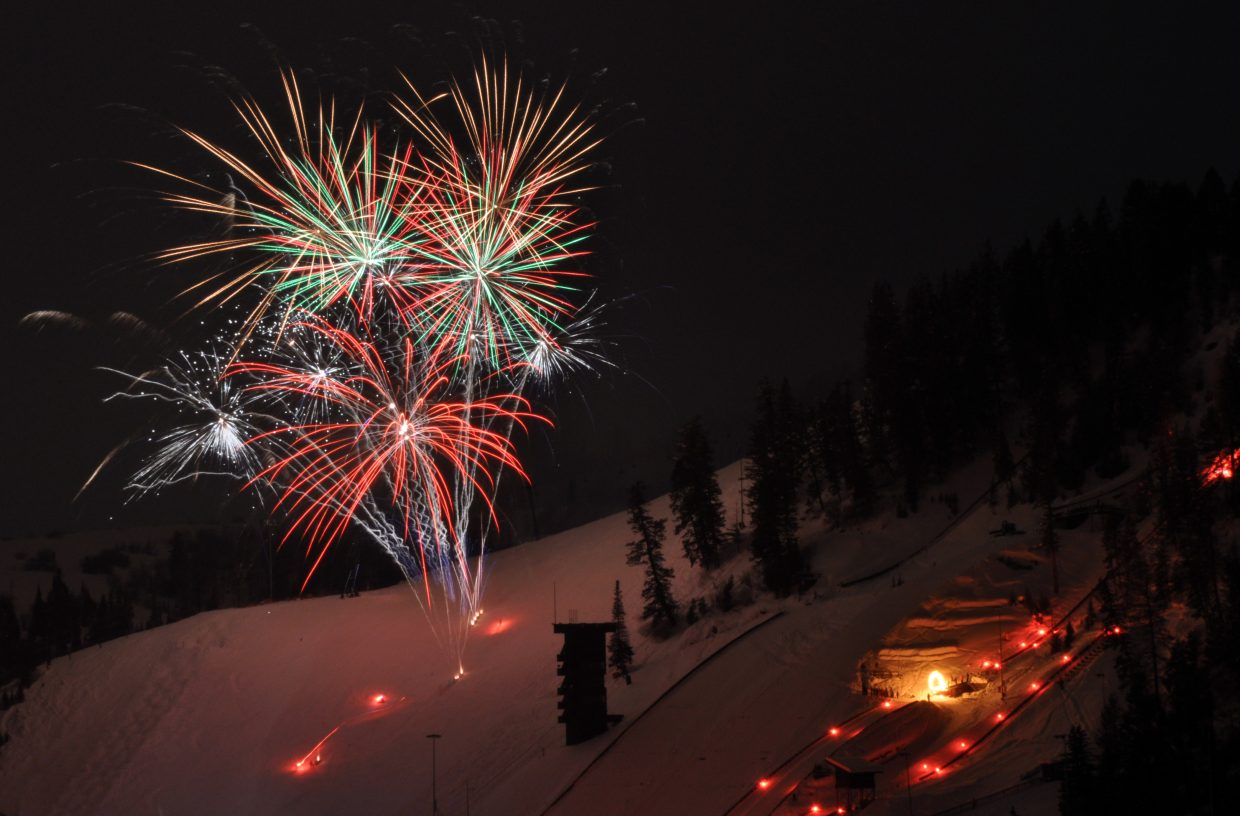 Steamboat Springs Winter Sports Club athletes do jumps as fireworks explode over Howelsen Hill during the 101st Winter Carnival.