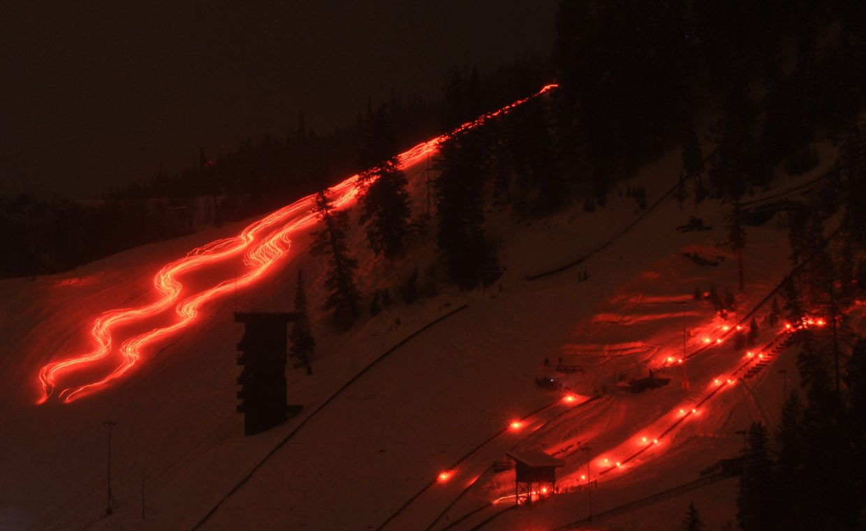 Steamboat Springs Winter Sports Club athletes stream down Howelsen Hill carrying torches as others go off a jump.