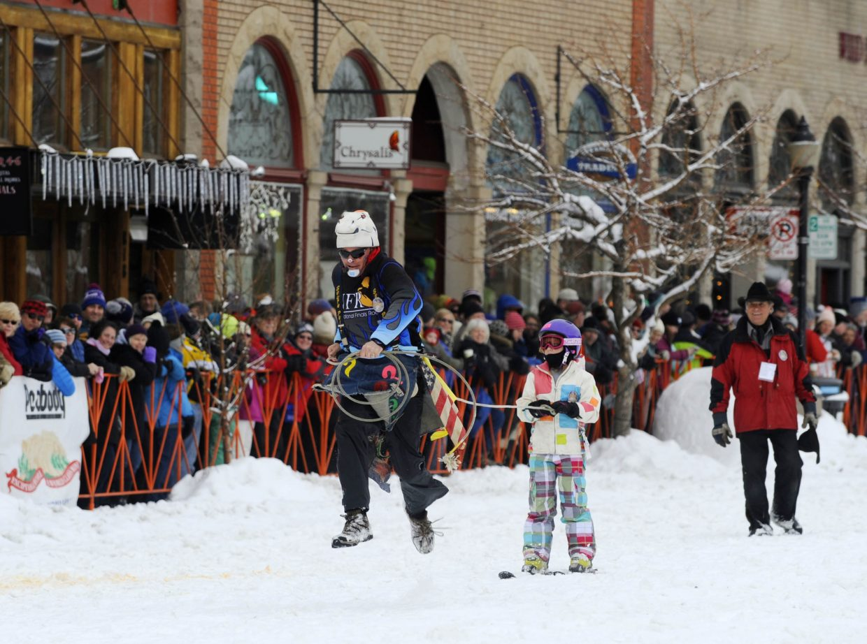 Rodeo clown J.W. Winklepleck helps pull a skier to the finish line during the Winter Carnival street events Saturday.