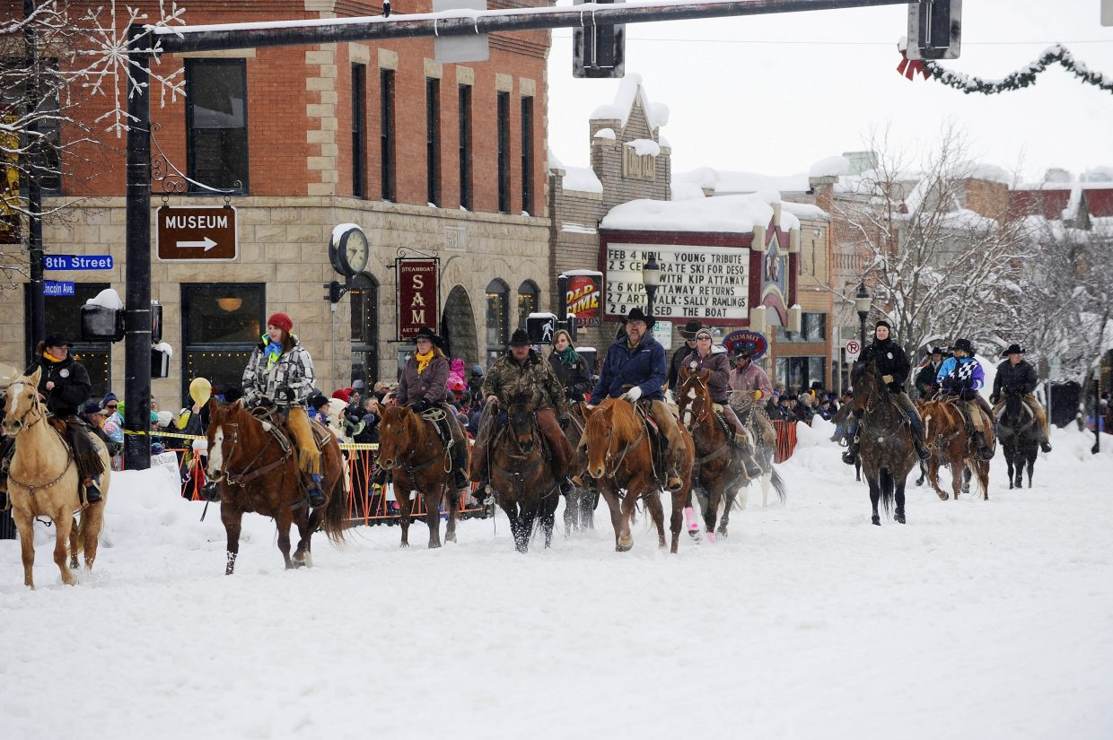 Local ranchers ride their horses down Lincoln Avenue during the Winter Carnival street events Saturday.